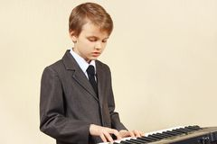 Little beginner musician in a suit playing electronic synth Stock Image