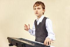 Little beginner pianist play the keys of electronic organ Stock Photos