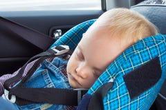 Little behandla som ett barn att sova i ett bilsäte Royaltyfri Bild