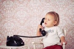Little behandla som ett barn med den gammala tappningtelefonen Arkivbilder