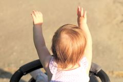 Little, belittle, beautiful, smiling, cute redhead baby in a sleeveless shirt in a pram out-of-doors raises his hands up and. Little, beautiful, smiling, cute royalty free stock photo