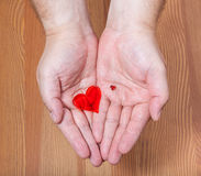 Little and big hearts in male hands. With wooden background Royalty Free Stock Photography