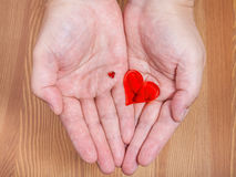 Little and big hearts on male palms. With wooden background Royalty Free Stock Photos