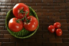 Little and big tomatoes in green basket Stock Image