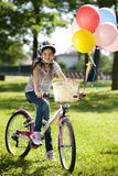 Little biker with balloons. Little girl on her bike with colorful balloons Royalty Free Stock Photography