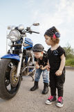Little biker repairs motorcycle on road Stock Photos