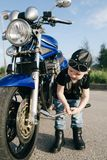 Little biker repairs motorcycle on road Royalty Free Stock Photography