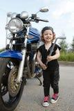 Little biker repairs motorcycle on road Stock Image