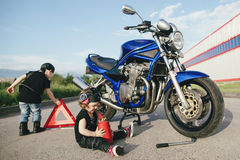 Little biker repairs motorcycle on road Royalty Free Stock Photo
