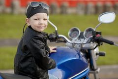 Little biker on road with motorcycle Stock Photography