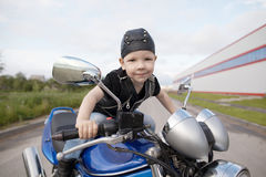 Little biker on road with motorcycle Stock Photo
