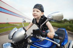 Little biker on road with motorcycle Royalty Free Stock Images