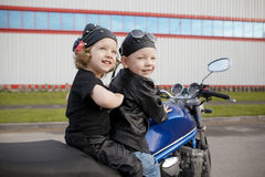 Little bikers on road with motorcycle Stock Photos