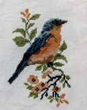 Little bird with blue and pink feathers sitting on a branch with flowers embroidery royalty free stock photography