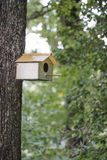 Little bird house on tree in forest Stock Photography