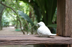 Little bird sculpture on the timber plank Stock Photography