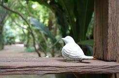 Little bird sculpture on the timber plank Stock Photography