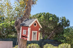 Little Birdhouse over wooden table outdoors in garden Stock Image