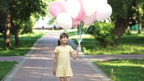 Little birthday girl is walking with a huge bunch of balloons in the summer park. Children run through the park with a huge bunch of colorful balloons. two stock video footage