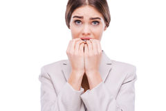 A little bit nervous about this business. Nervous young businesswoman biting her nails while standing against white background stock photo
