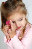 Little bitty heart. Little toddler girl holds a heart in her hand Royalty Free Stock Photography