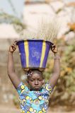 Little Black African Girl Outdoors With Big Heavy Sink. Candid shot of black African children outdoors in Bamako, Mali. By buying this image you support our Royalty Free Stock Photography