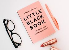 Little Black Book Surrounded With Pink Click Pen, Red Lipstick, and Black Wayfarer Eyeglasses Royalty Free Stock Photo