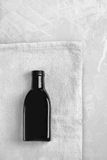 Little black bottle lays on a gray rag. On a light table Royalty Free Stock Photos
