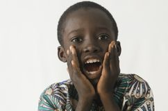 Little black boy surprised and excited with white isolated backg. Beautiful shot of African children taken in a studio in Bamako, Mali Royalty Free Stock Images