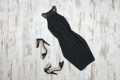 Little black dress and shoes. Wooden background, fashionable con. Cept stock image