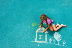 Little black girl drawing chalk house image. Nice looking black girl drawing house sun and trees with chalk on playground Stock Image