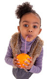 Little black girl drinking orange juice. With a straw Royalty Free Stock Photo