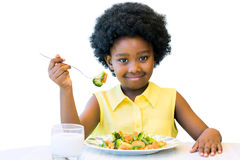 Little black girl eating healthy vegetable meal. Close up portrait of cute african girl with afro hairstyle eating healthy vegetable dish. Isolated on white Stock Photo