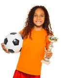 Little black girl holding soccer ball and prize. Close portrait of happy African black girl with curly hair holding soccer ball and winners prize cup wearing Stock Photos