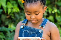 Little black girl looking at tablet outdoors. Close up portrait of little african girl playing with digital tablet outdoors Royalty Free Stock Photo