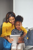Little black girl and mom with tablet. Sitting in sofa smiling Royalty Free Stock Photo