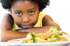 Little black girl pulling up nose for vegetables. Close up face shot of little afro american girl with negative moody face expression at dinner table. Kid Royalty Free Stock Photo