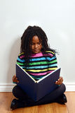 Little black girl reading book Stock Photo