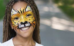 Little black girl with tiger face painting stock photo