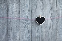 One little heart on a rope hang on a pink rope on a wooden gray background Stock Photos