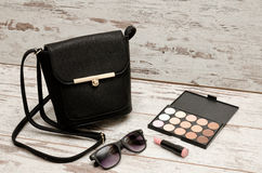 Little black ladies handbag, sunglasses, eyeshadow palette and lipstick on wooden background. Fashion concept stock photos