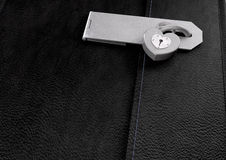 Little Black Leather Locked Diary. A closeup of a black leather diary secured by a hasp and a heart shaped padlock Stock Images