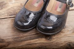 Little black shoes on wooden background stock photo