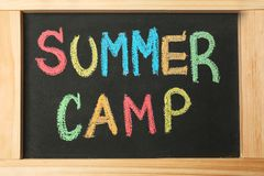 Little blackboard with inscription SUMMER CAMP. Chalked in different colors, closeup Royalty Free Stock Image
