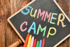 Little blackboard with text SUMMER CAMP chalked. In different colors on table, top view stock photography