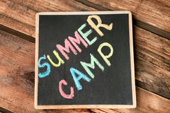 Little blackboard with text SUMMER CAMP. Chalked in different colors on table, top view Stock Photography