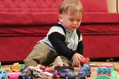 Little blond baby boy. Playing with toys at home stock image