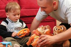 Little blond baby boy. Playing with toys at home with his father royalty free stock images