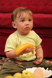 Little blond baby boy. Expressive blond baby boy amazed with a banana in hand Stock Photo
