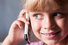 Little blond beautiful girl with mobile phone Royalty Free Stock Photos